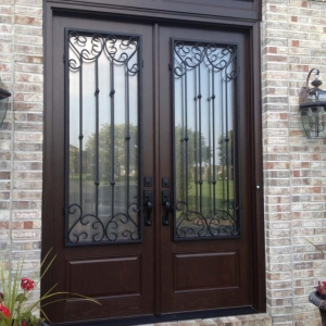 dark brown front french door with glass transom windows black iron scroll work with red brick house