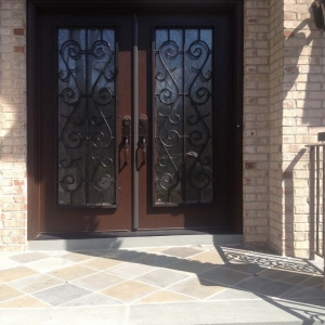 Dark brown front door with black iron scroll work with red brick house