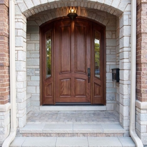 Natural wood curved front door with stone on a red brick house
