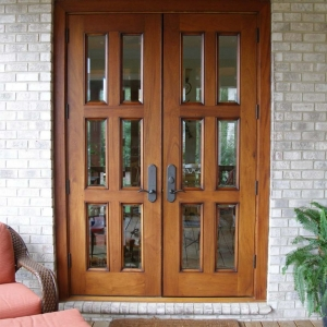 natural wood french style front door with glass on a brick house