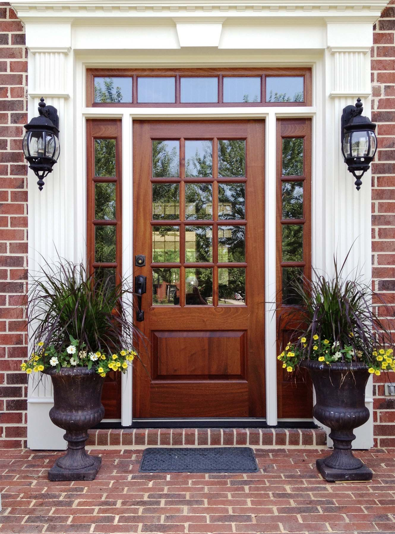 natural wood stained front door with transoms white trim on a red brick house beautiful porch plants