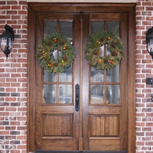 natural wood french front door with glass on a red brick house