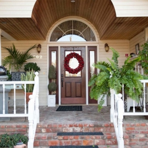 stained wood front door with glass transoms wood soffet red brick front porch house