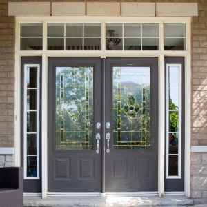 dark gray french style front door with glass transoms on a brick house