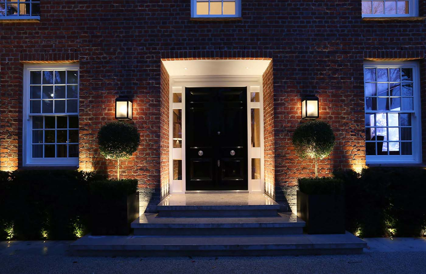 black front door with glass transoms and white trim beautiful landscaping brick house at night