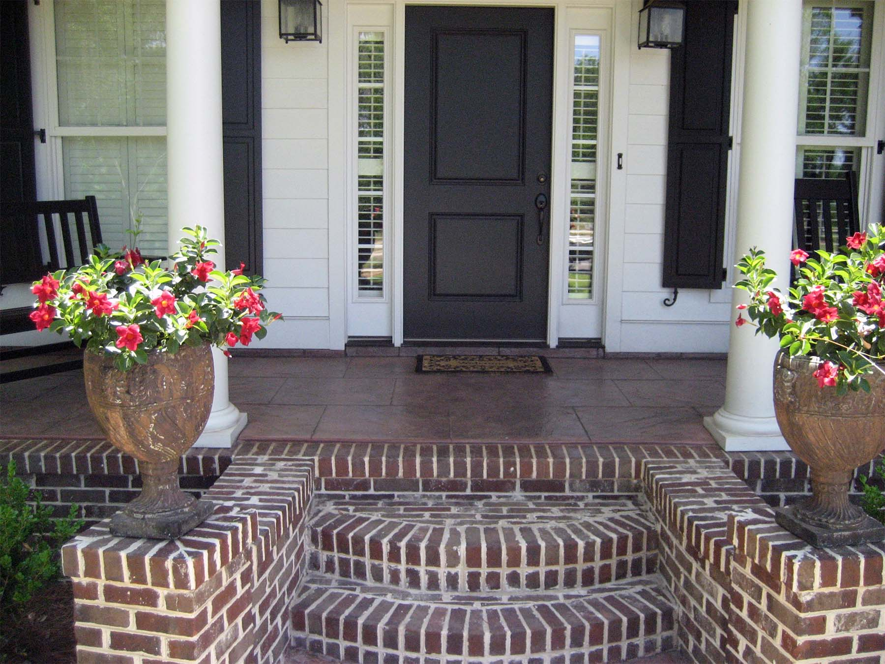 black front door with glass transoms white house with black shutters red brick front steps