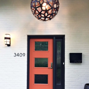 modern style orange front door with black trim and single transom on white brick house
