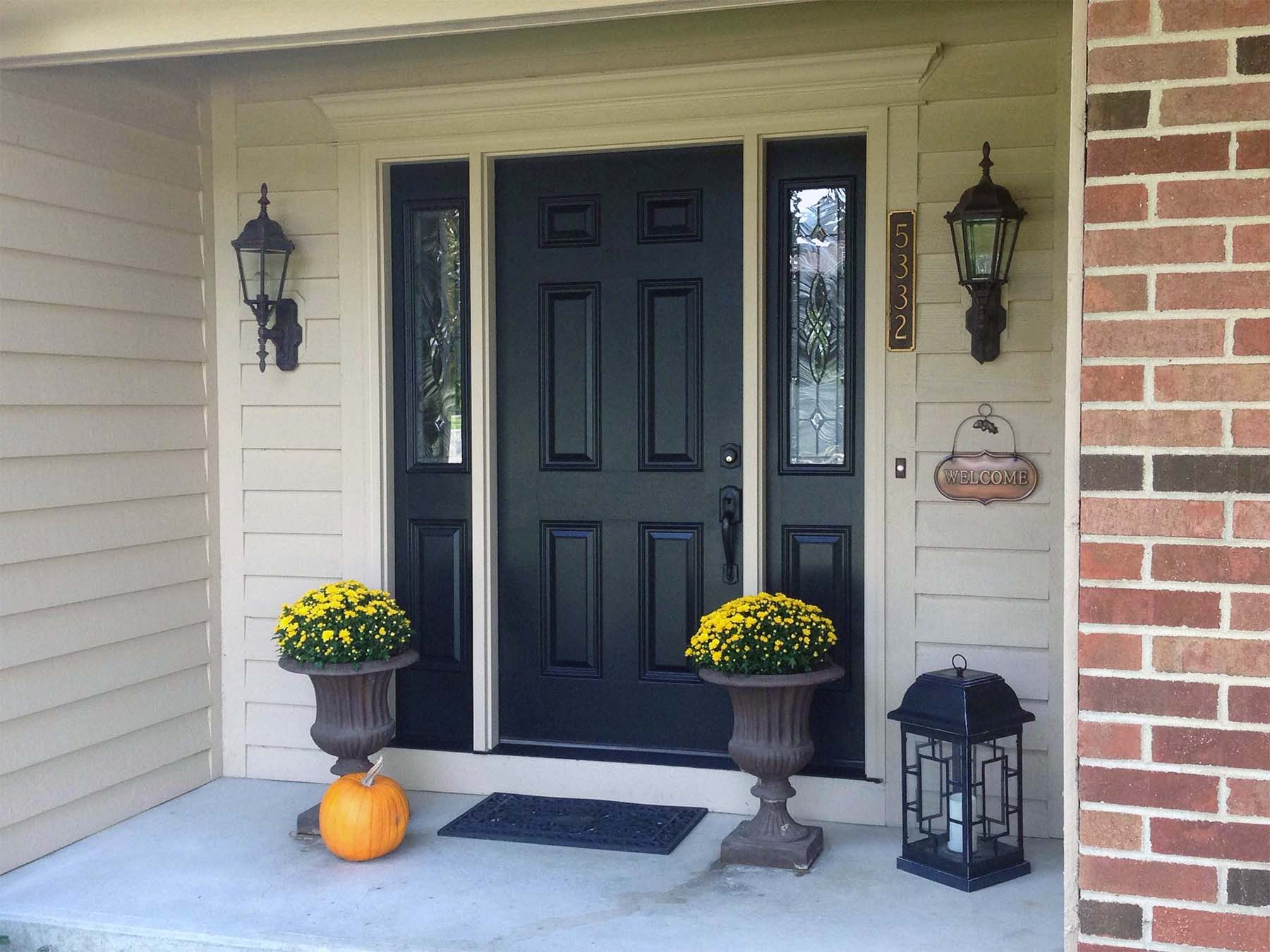 black front door with glass transoms with red brick house concrete front steps yellow porch flowers