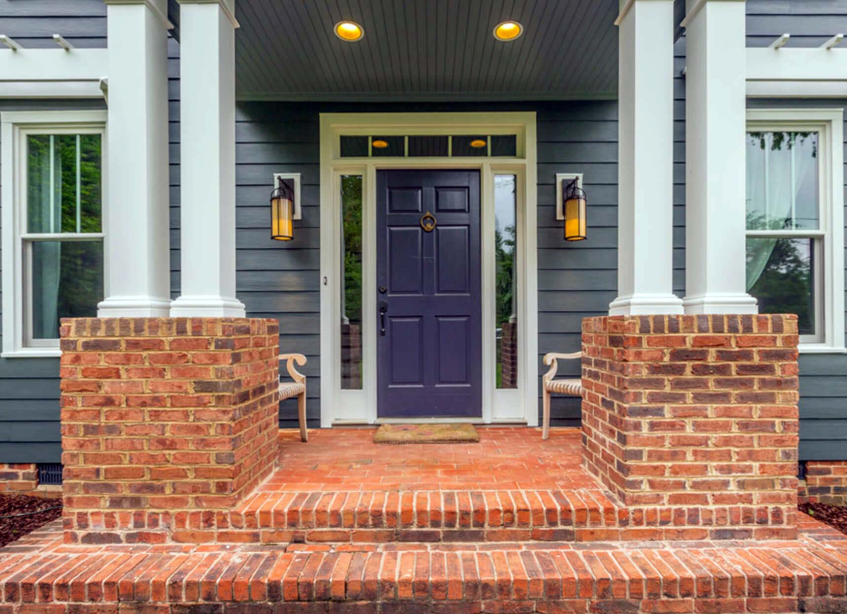 purple front door with glass transoms white trim blue siding with red brick columns front steps