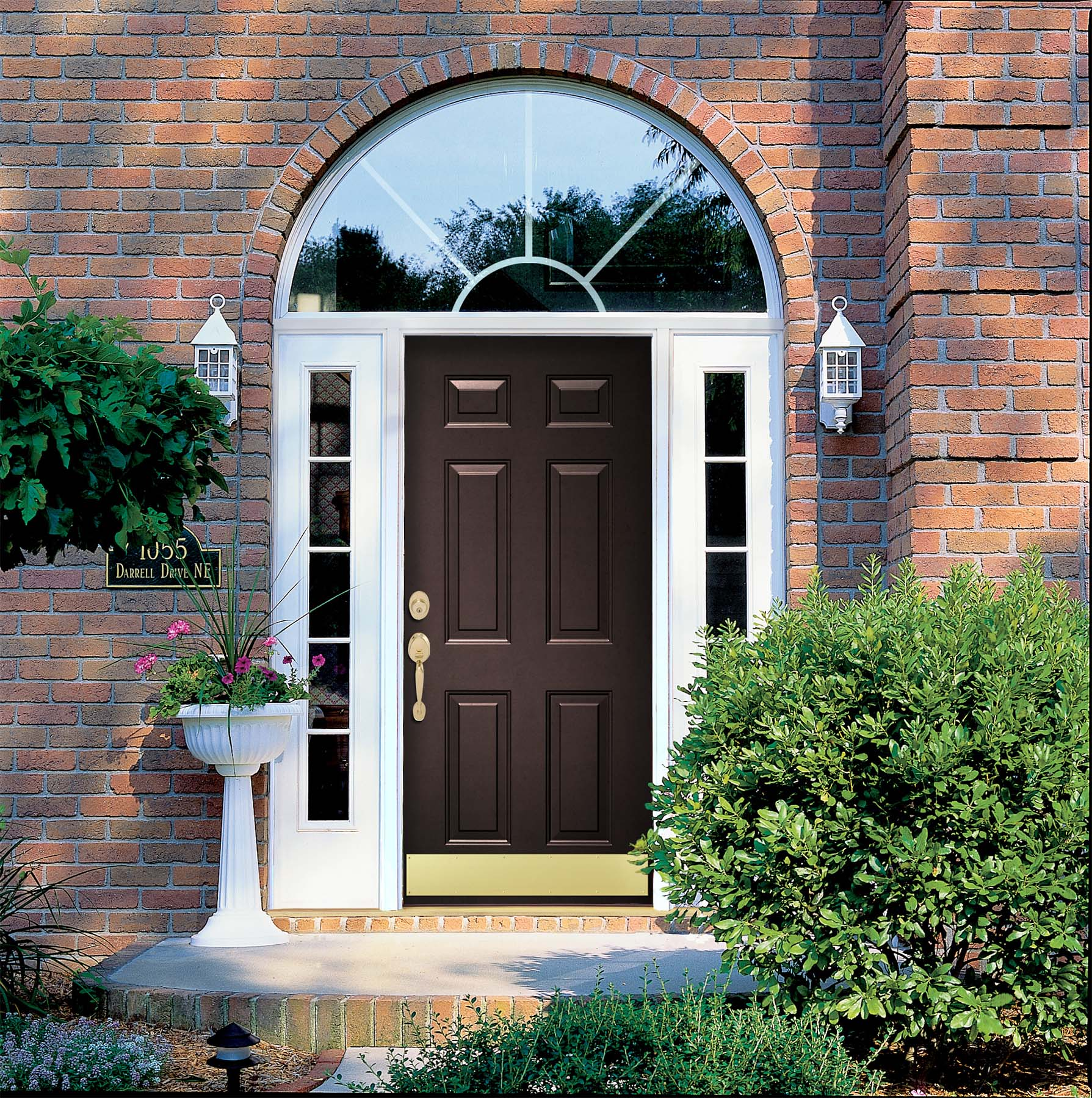 black front door with white trim glass transoms red brick house lots of plants white door lights