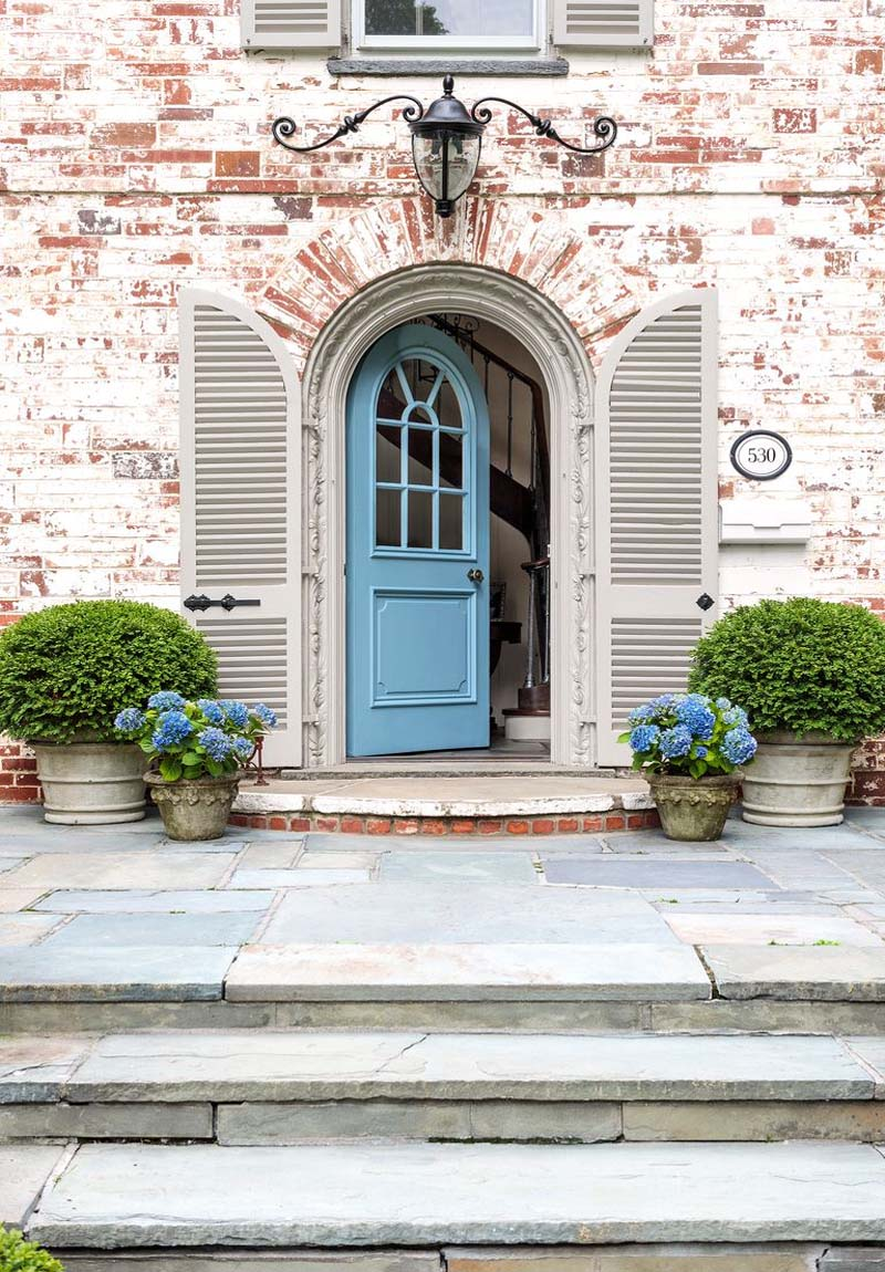 light blue front door with white washed red brick house blue stone patio and porch plants