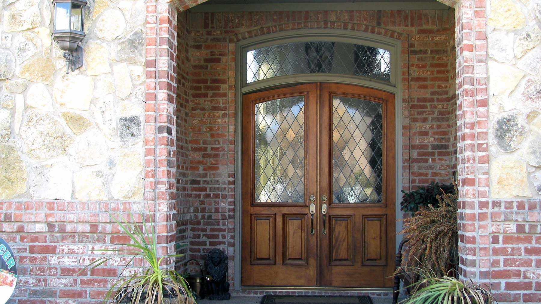 real wood front door with arched top and transom french style red brick house with real stone