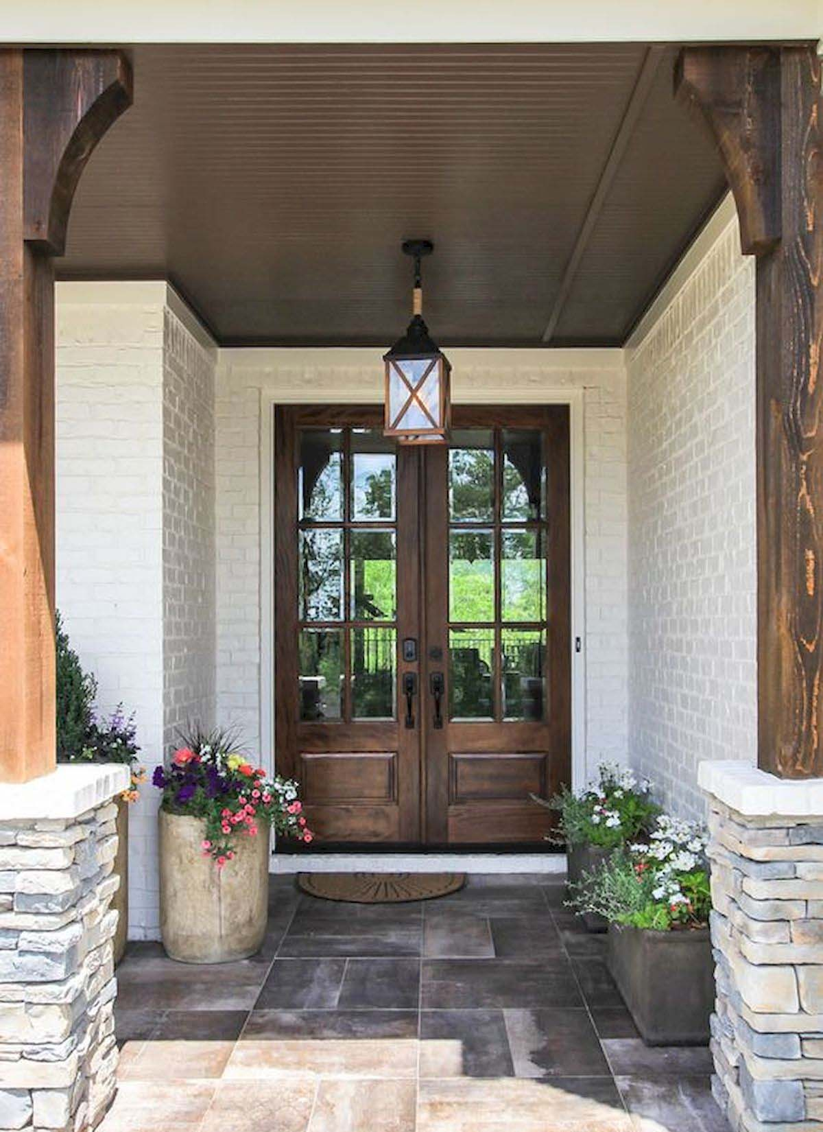 real wood front door with white brick house wood columns stone pillars