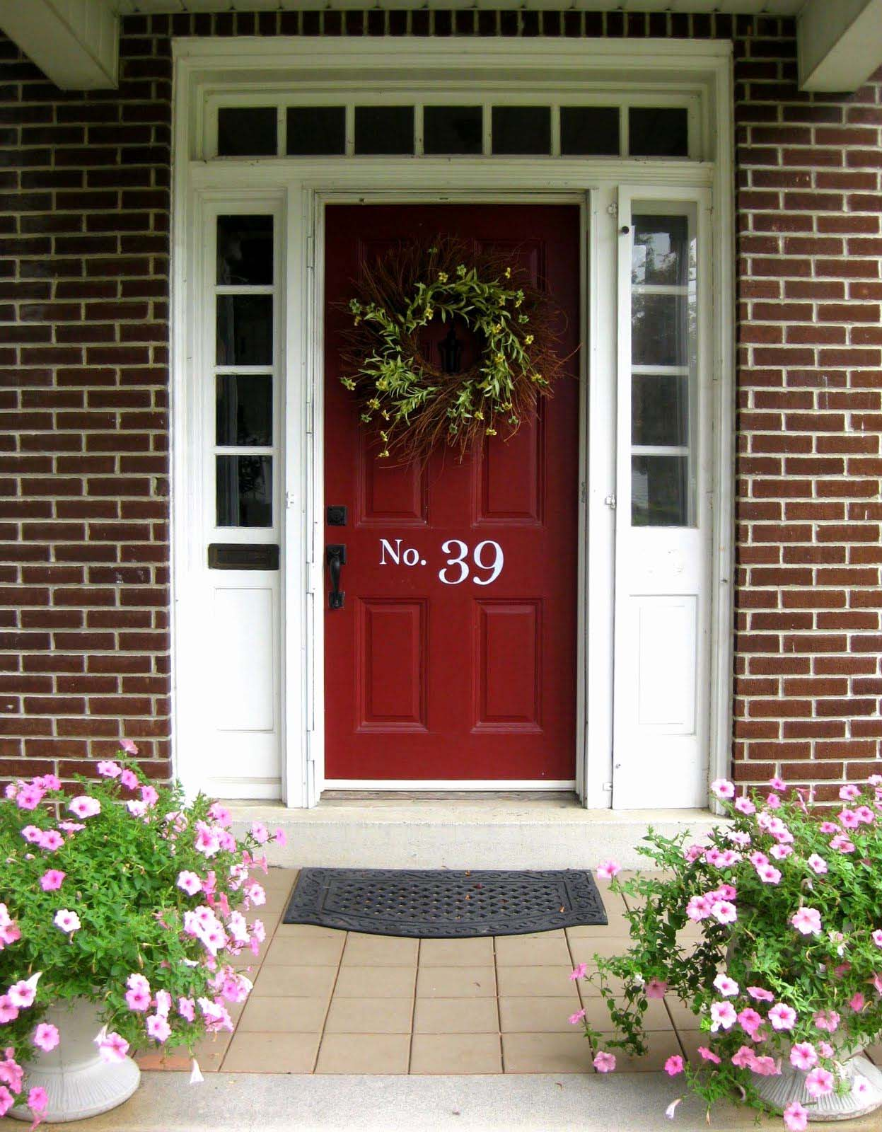 dark red front door with white trim and glass transoms red brick house colorful porch plants
