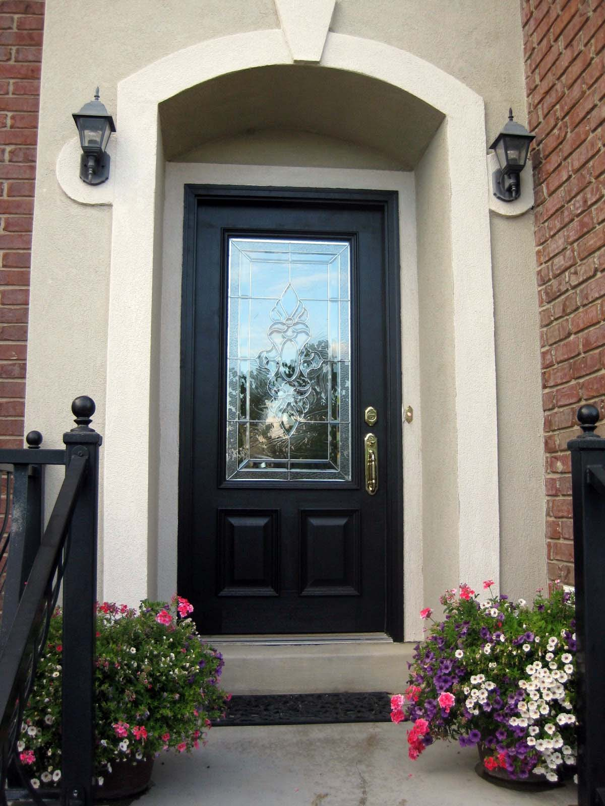 black front door with stucco surround gold hardware red brick house black iron railings