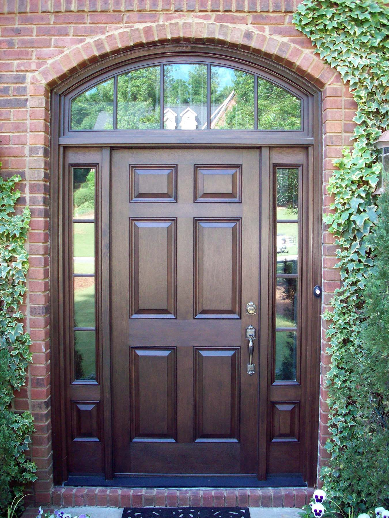 dark wood front door with arched glass transom red brick house green porch plants
