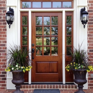beautiful Natural wood front door with glass transoms white trim red brick house colorful porch plants
