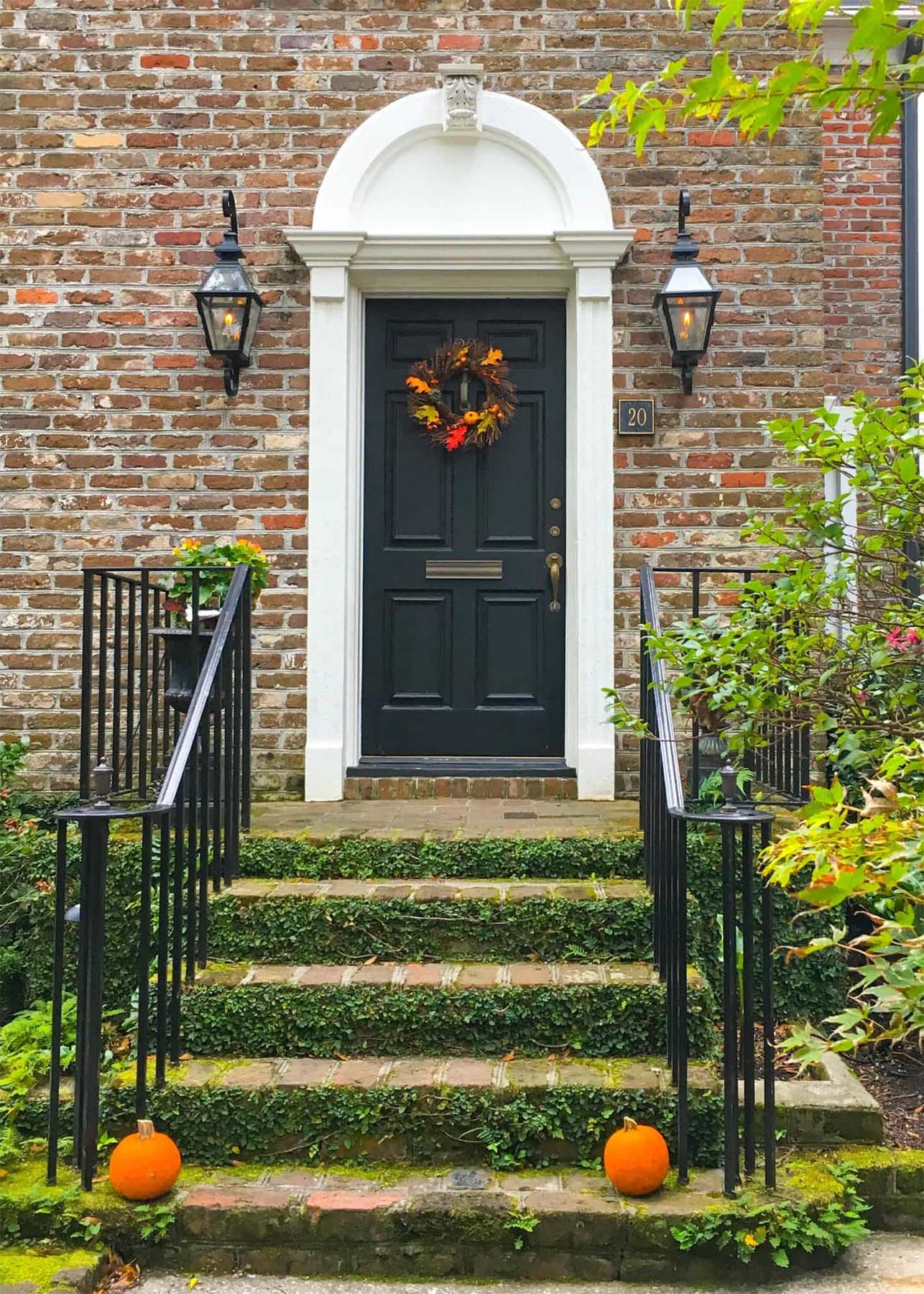 beautiful black front door on a red brick house white trim black iron railings lots of plants