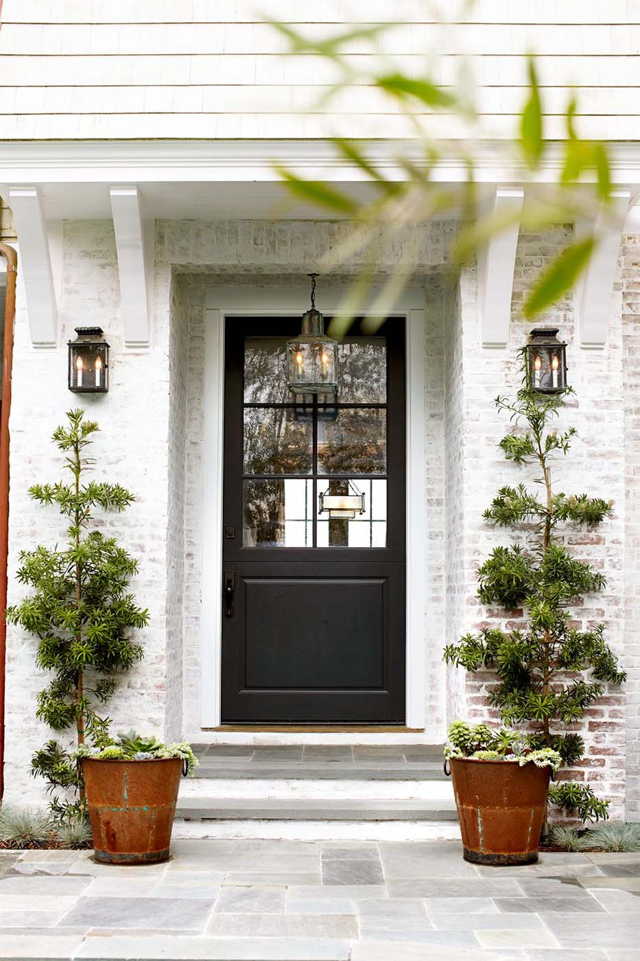 Black front door with white washed red brick and white trim blue stone patio and porch plants