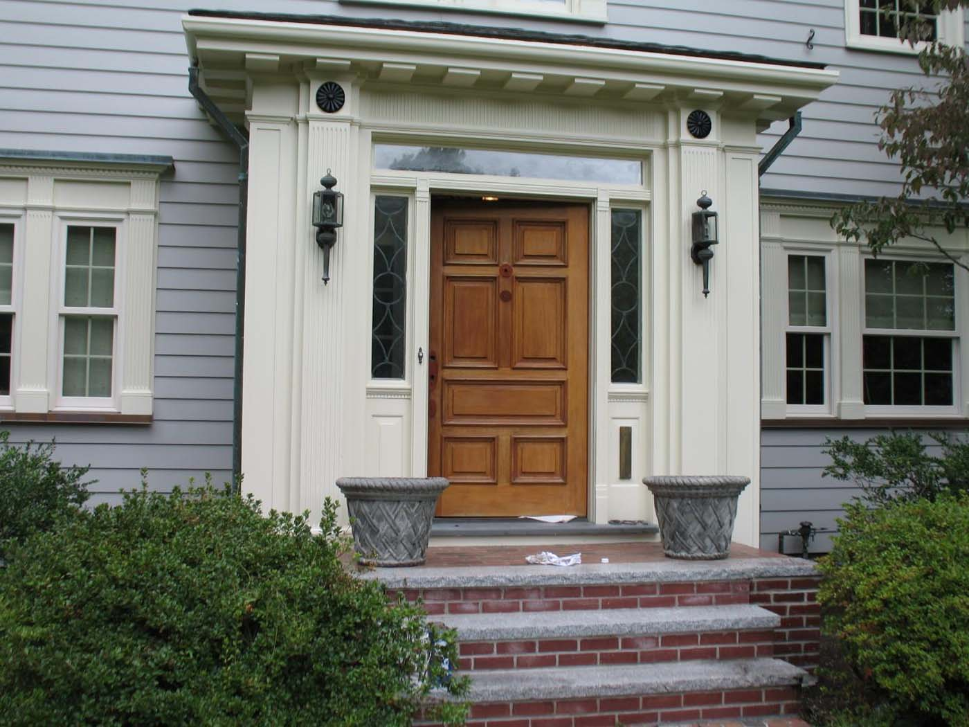 real wood front door with transoms and cream trim red brick stoop and limestone