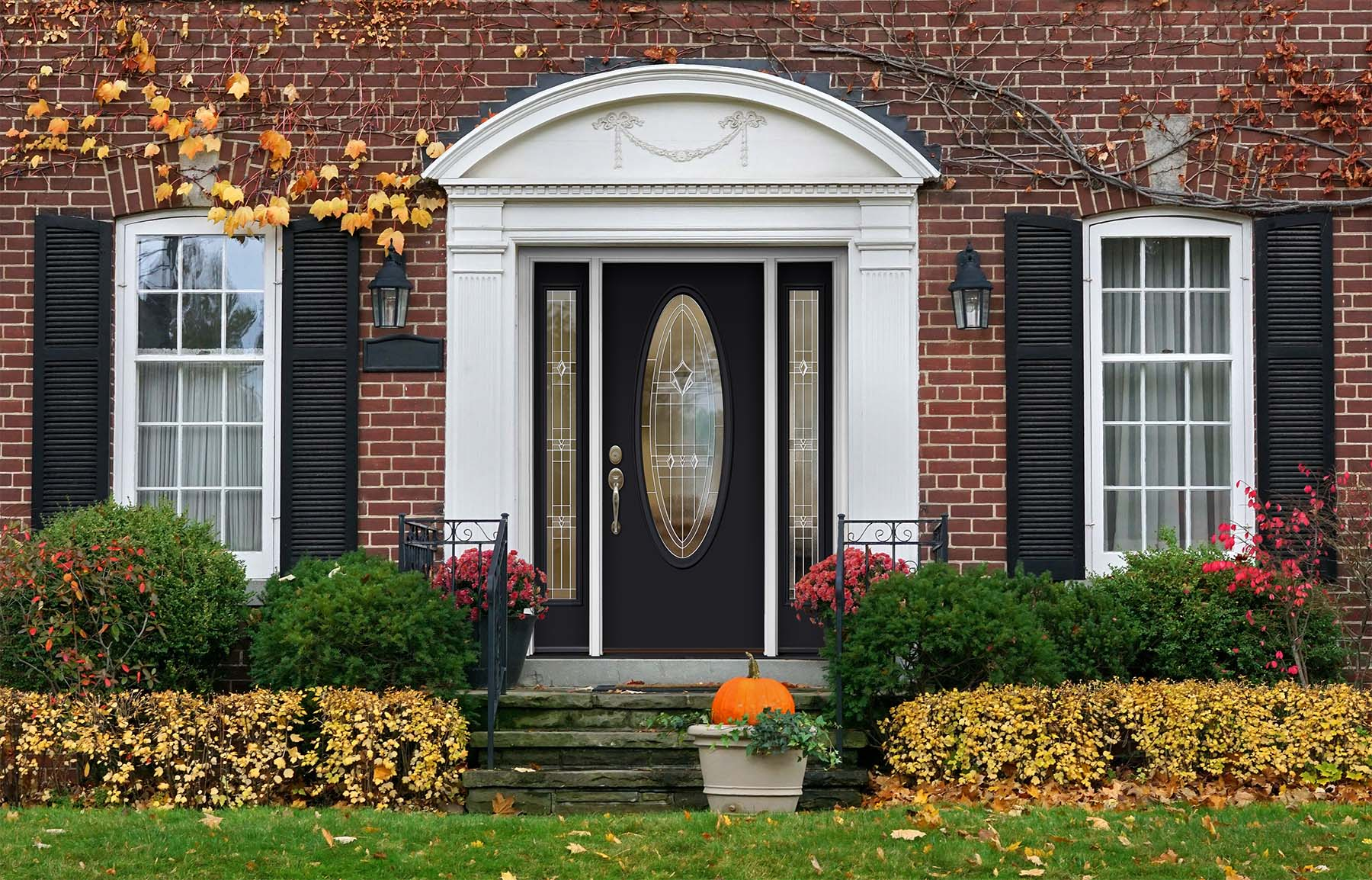 black front door with red brick house and white trim glass transoms and oval glass design