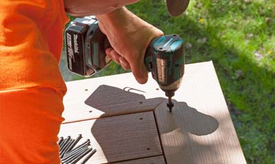 Cortex hidden deck fastener screws being installed with a drill and cortex plugs