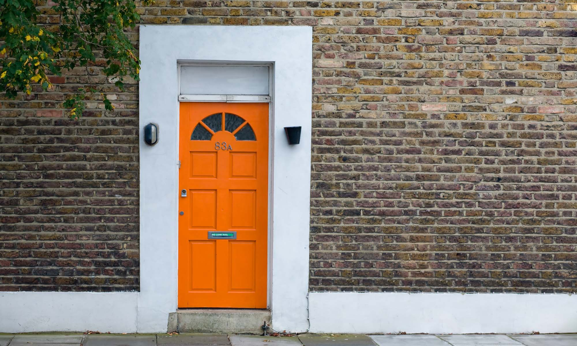 orange color front door with white trim and red brick house