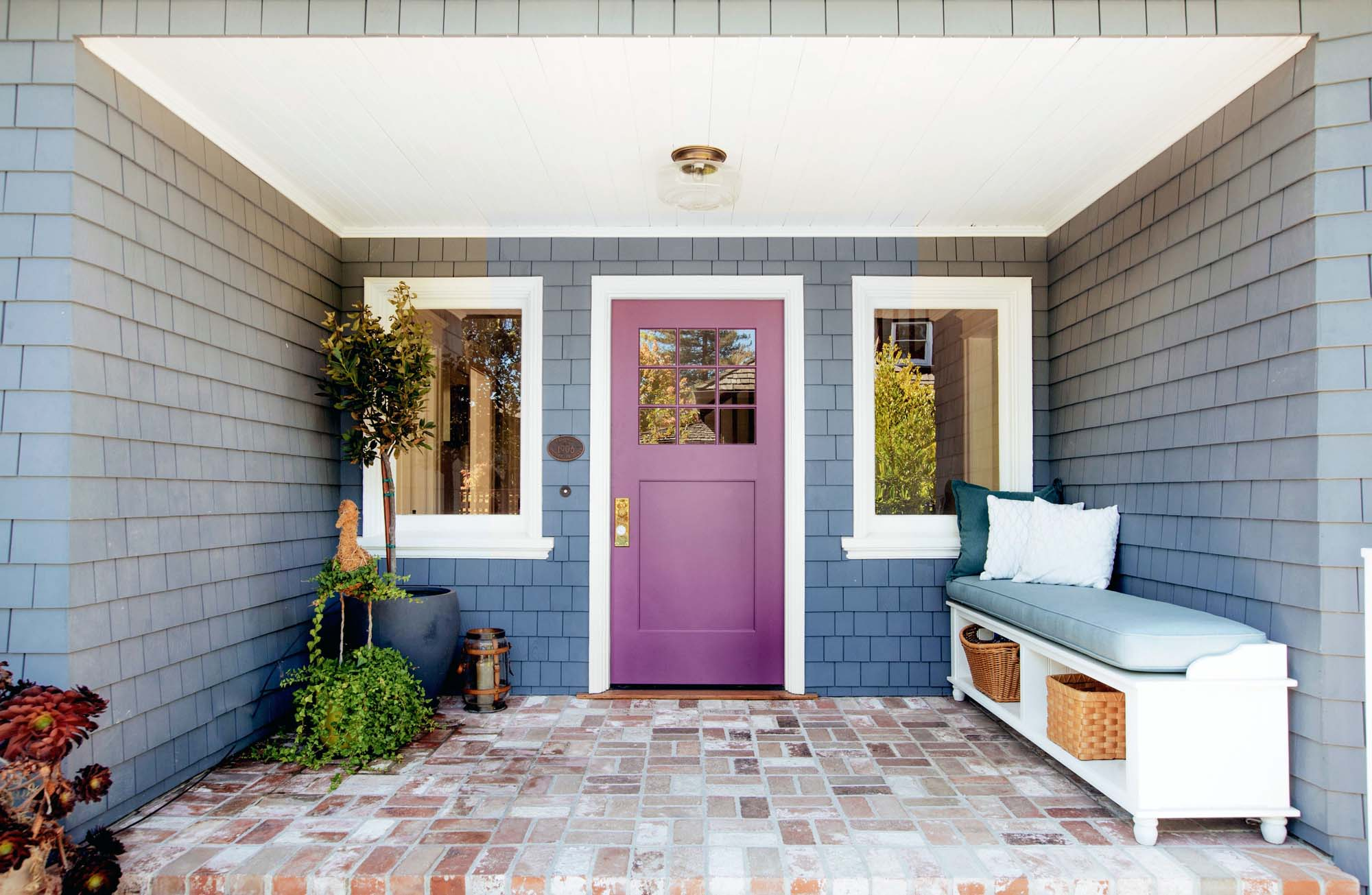 Plum purple front door with blue siding white trim and red brick