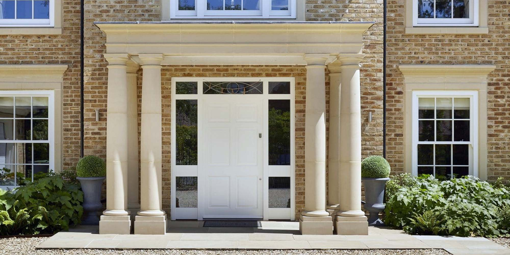 white front door color with beautiful stone columns stucco on an all red brick home