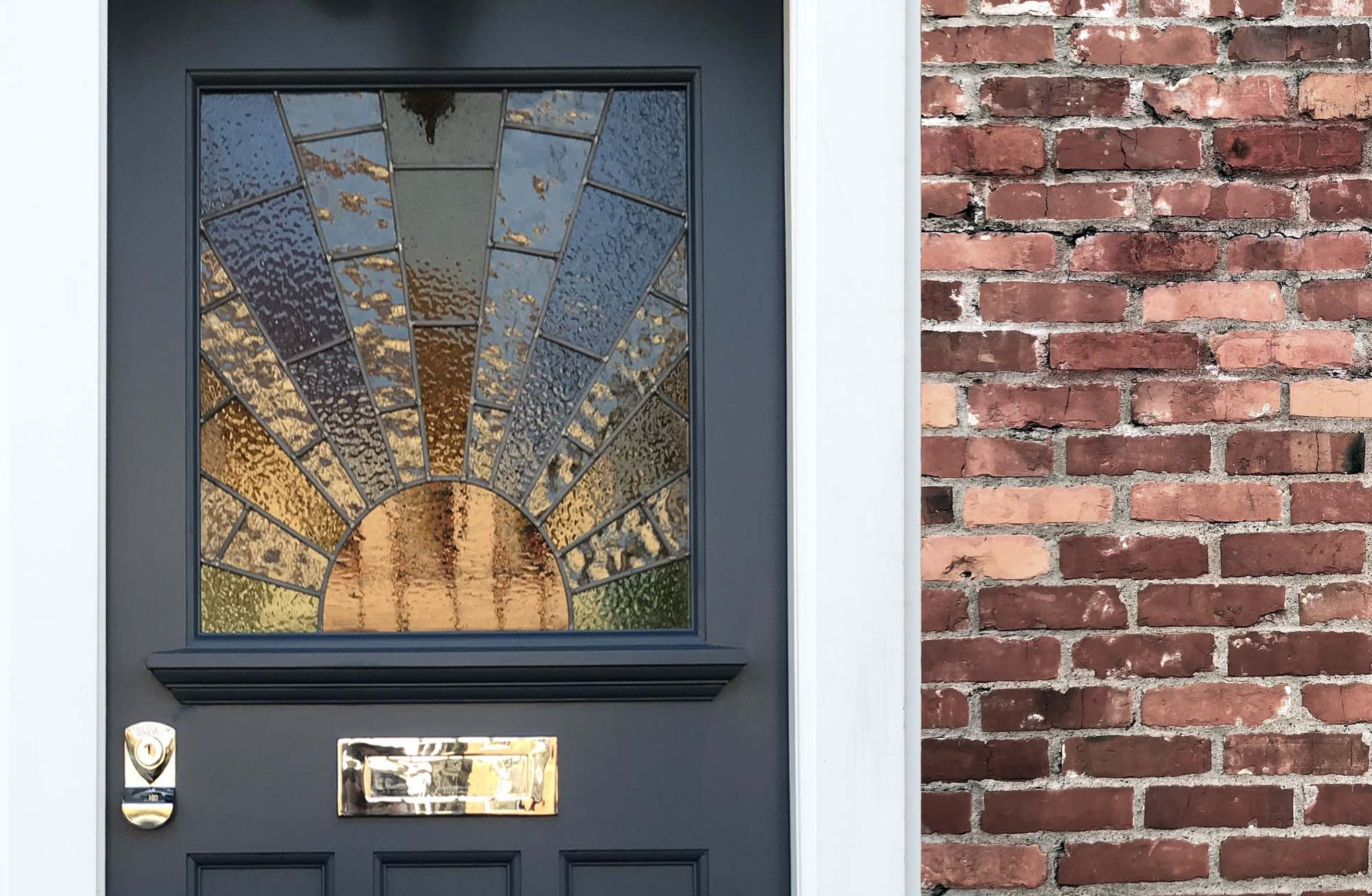 beautiful dark blue front door with brick star burst glass pattern gold hardware