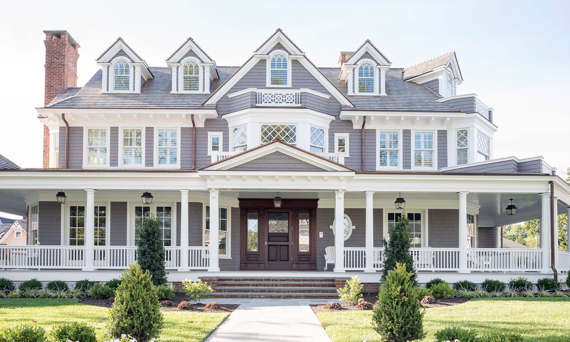 stunning gray and white custom home with dark wood front door and red brick