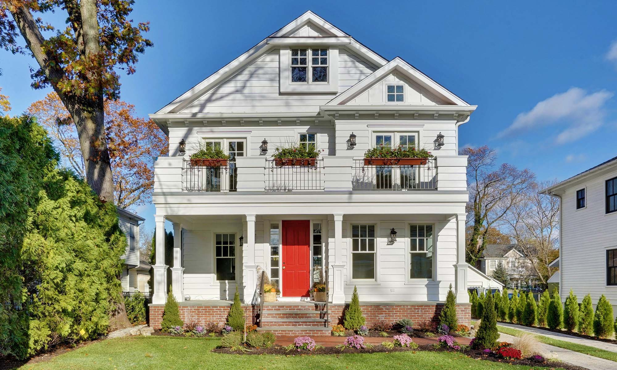 red brick home with white siding and a red front door