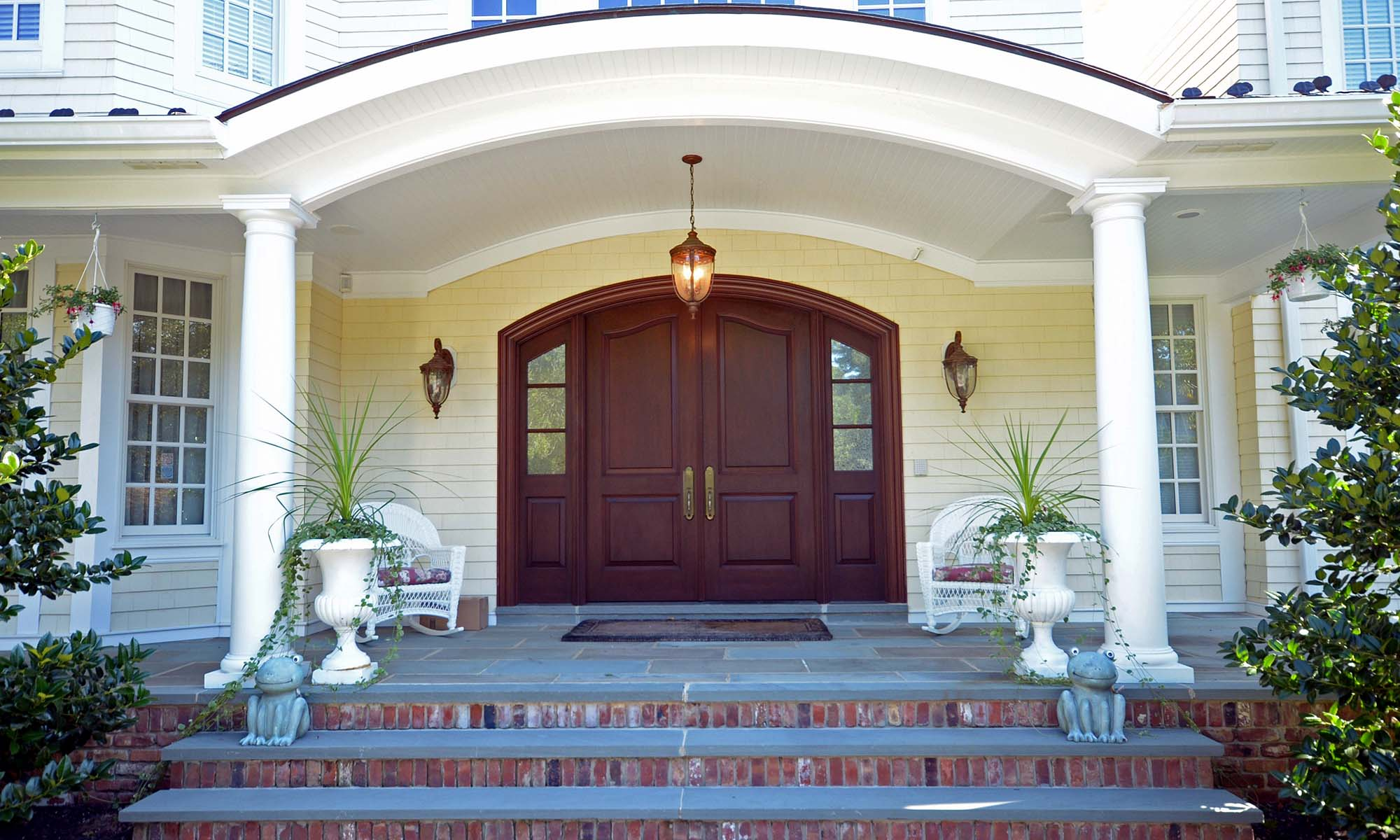 curved mahogany front door with yellow siding and white trim on a home with red brick