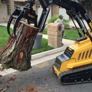 NJ Tree removal Service Picking up tree trunks with a machine
