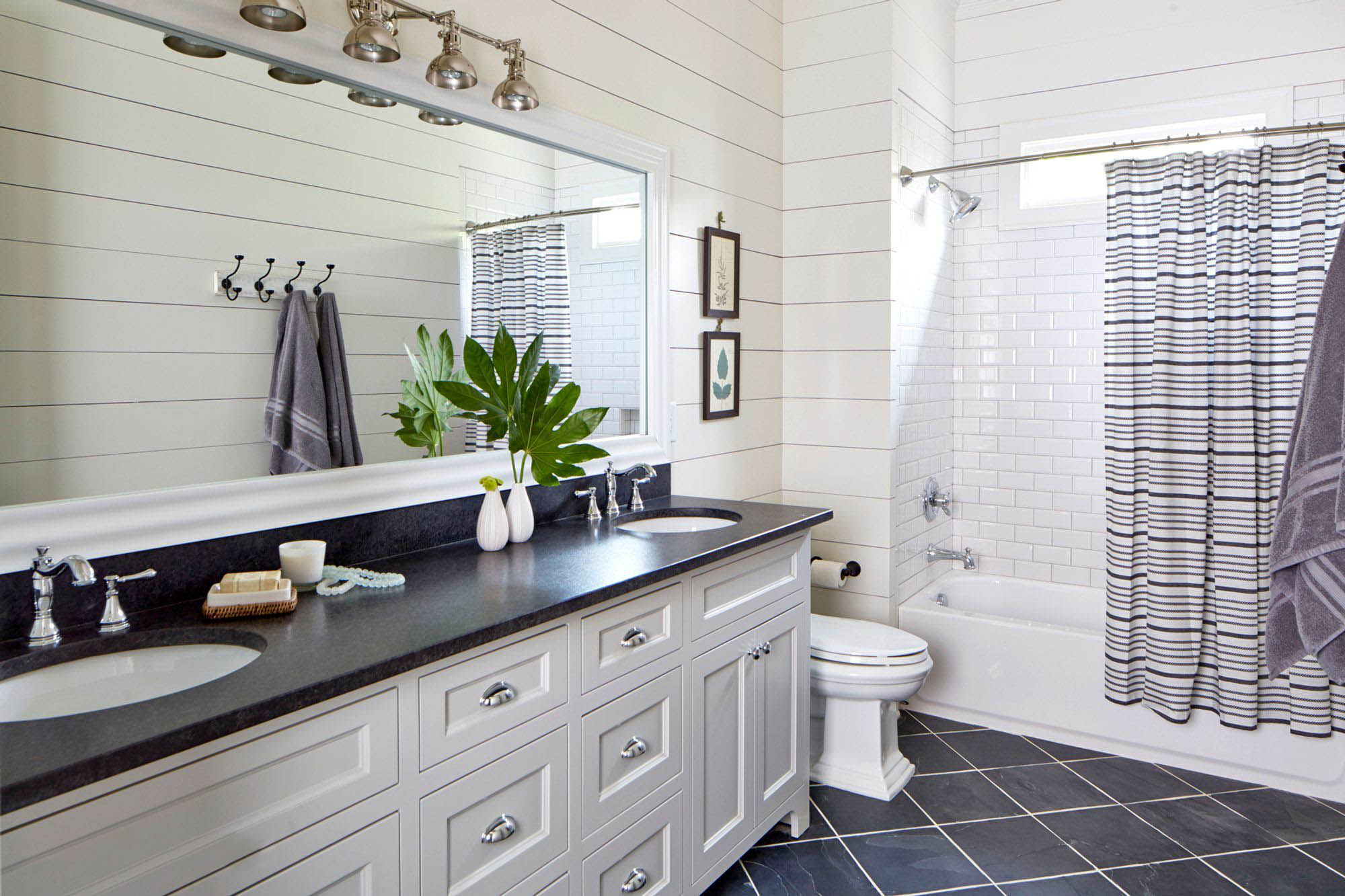 White bathroom with black granite countertops. Shaker style cabinets. White shower tile. White shiplap walls.
