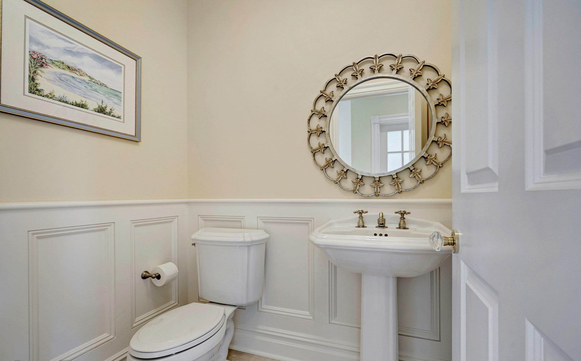 Beautiful 1/2 bath with white wainscoting. Colonial style trim. Light cream colored walls. White sink and toilet. What a nice, clean bathroom design.