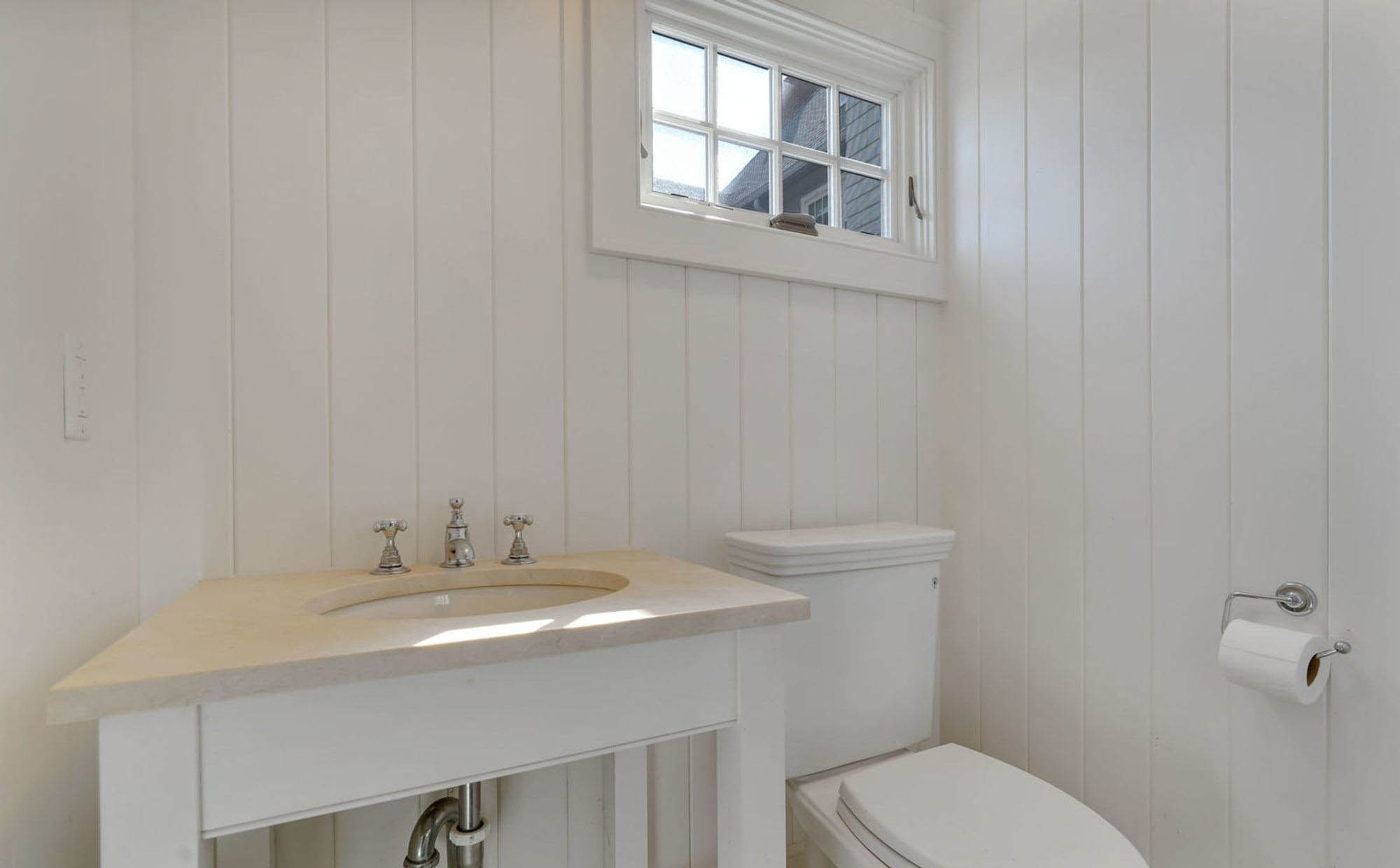 small half bath with vertical wall paneling. White wall, vanity and toilet with cream countertop
