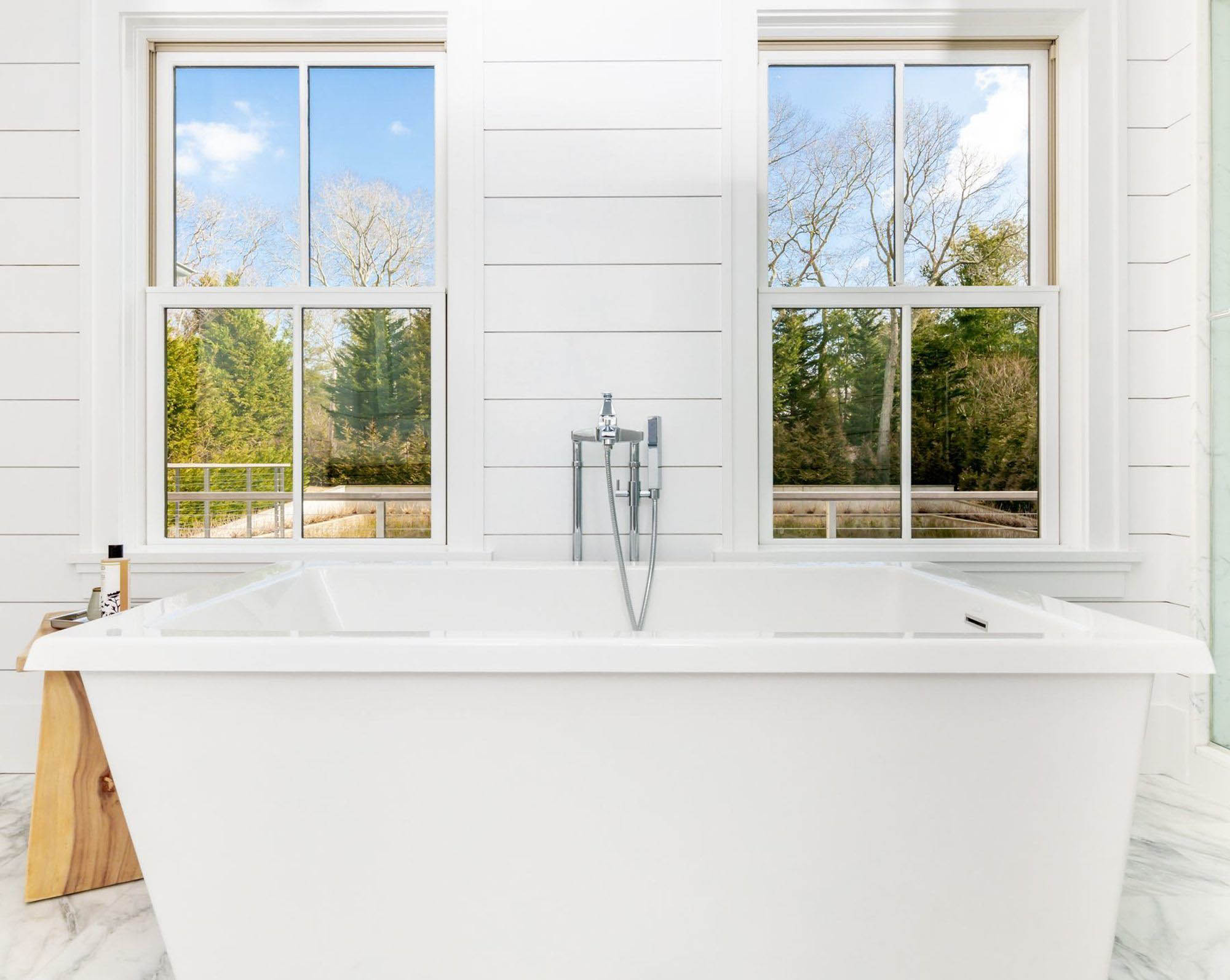 Modern marble bathroom with shiplap wall trim. White paneling and trim work. Large rectangle soaking tub with chrome faucet.