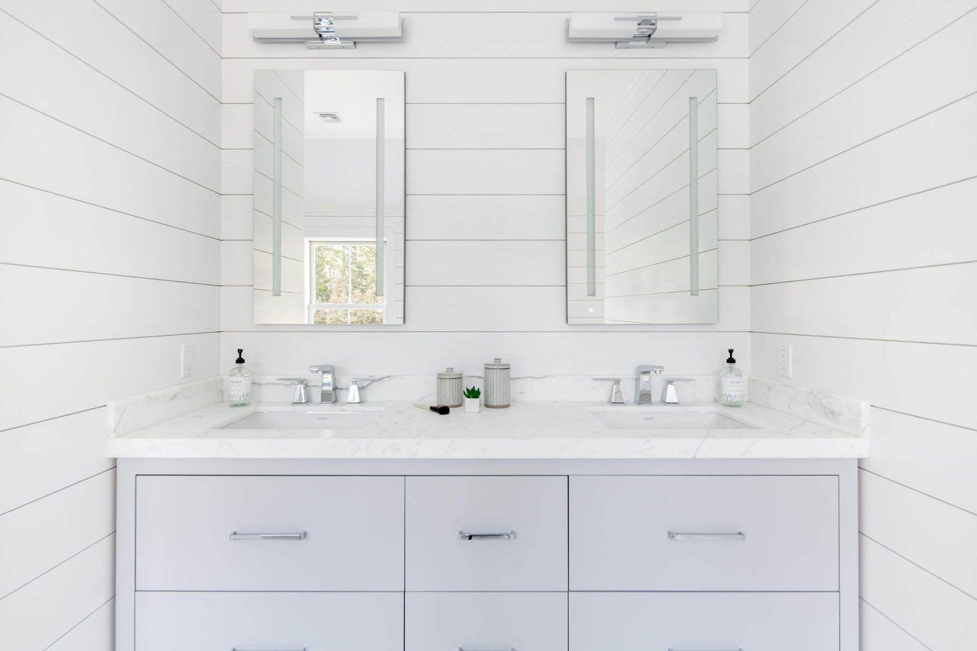 Beautiful modern bathroom design with shiplap wall trim. Double sink with marble countertop. Super clean vanity with flat faced drawers.