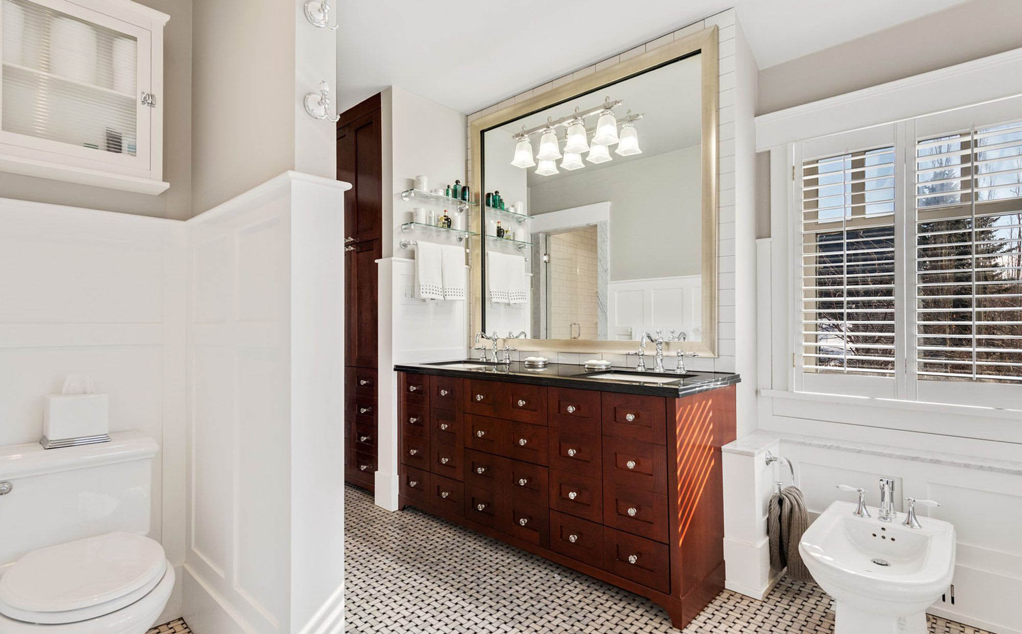 Beautiful master bathroom with box beam wainscoting design. White bathroom with wood vanity featuring lots of drawers.