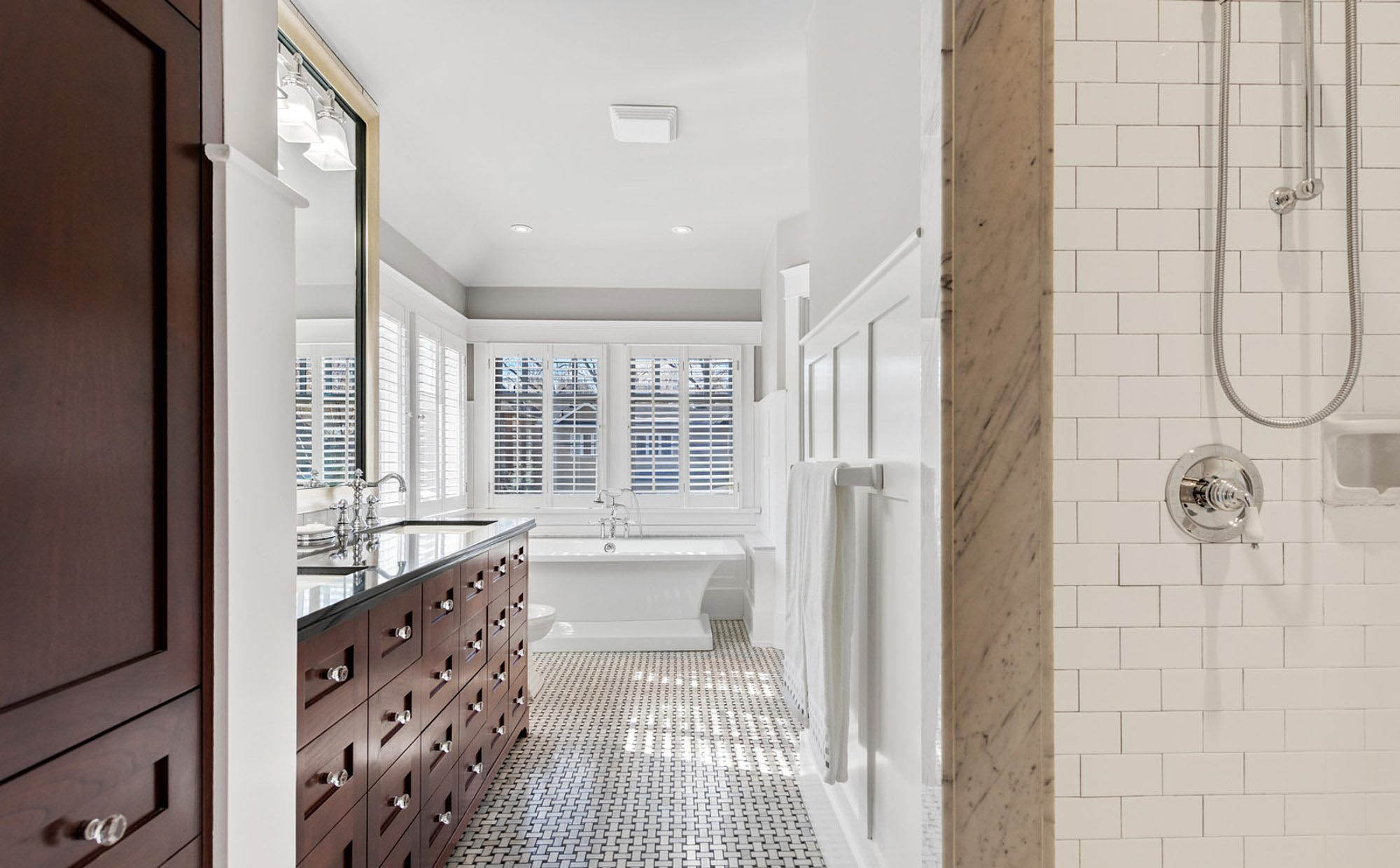 Beautiful master bathroom with box beam style wainscoting.Wood vanity with white wall trim. Warm gray walls.