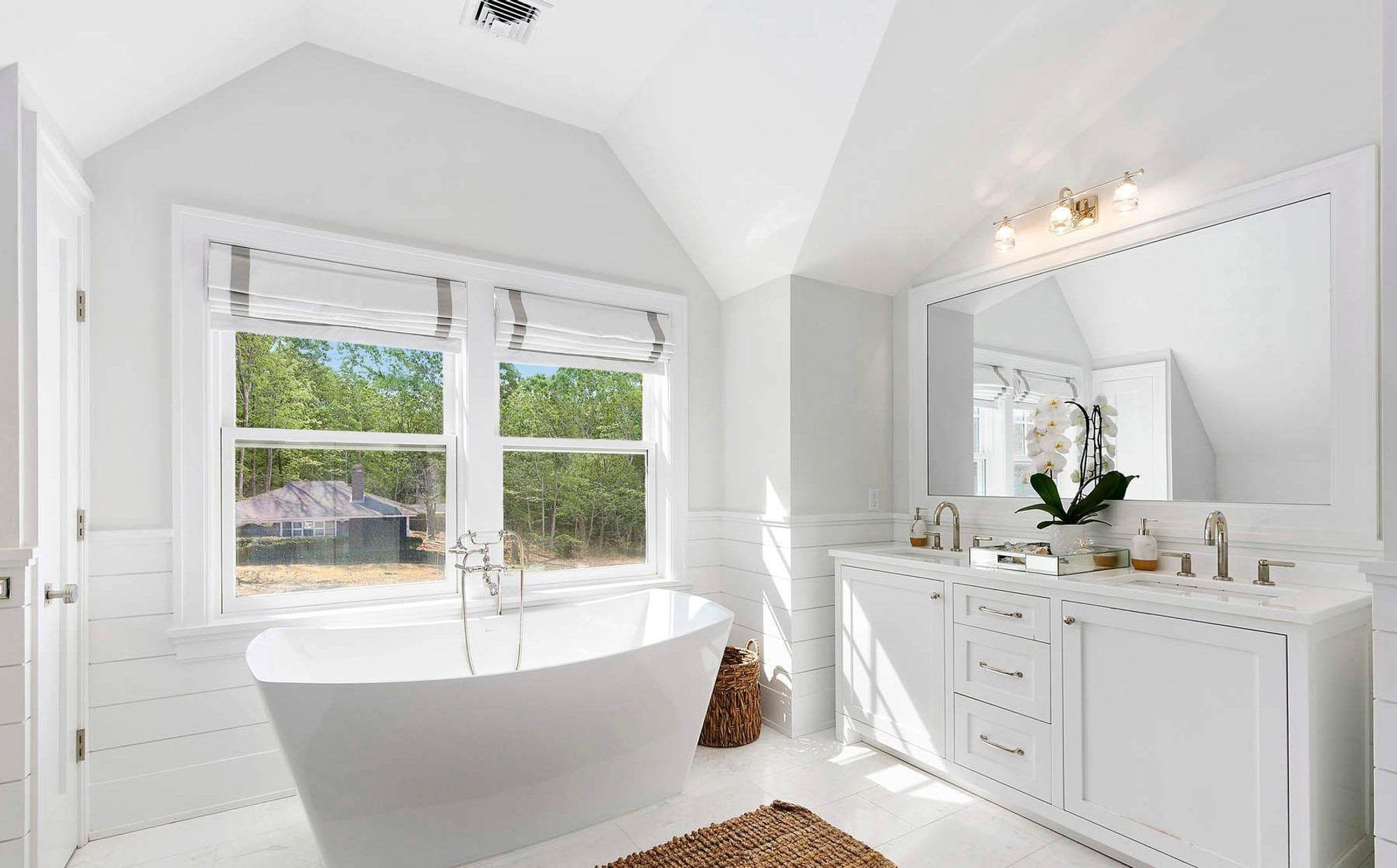 Another beautiful master bathroom design with shiplap wainscoting wall paneling. Shaker style cabinets with a freestanding soaking tub.