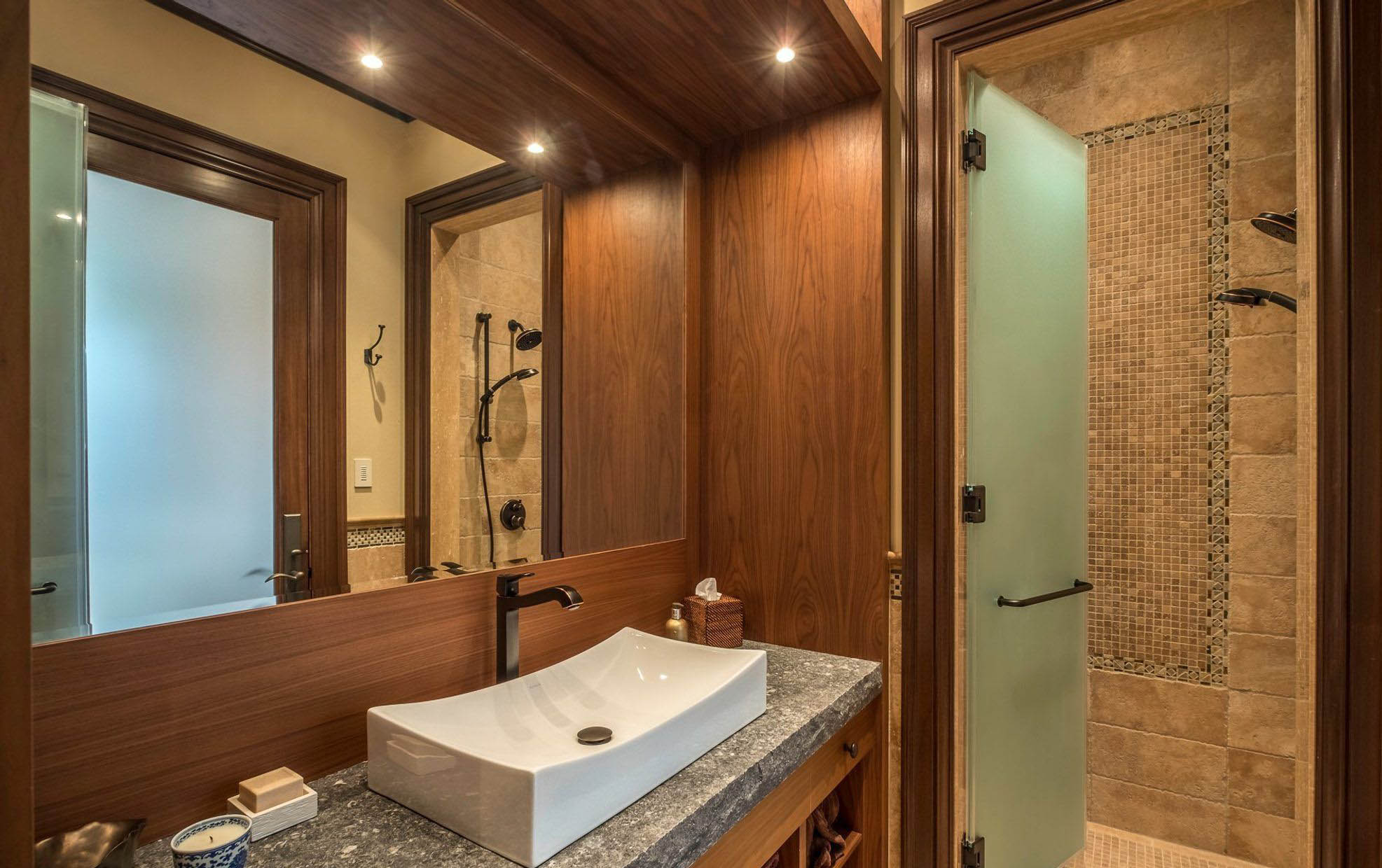 Master bathroom with exquisite wood wall paneling stained a rich medium brown with wood backsplash.