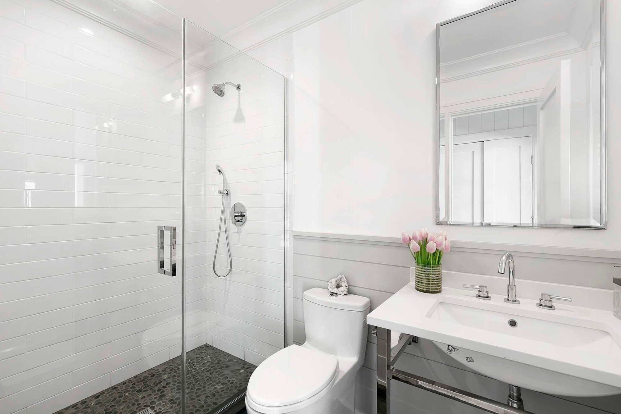 Full bath with horizontal shiplap wainscoting. In a medium sized bathroom horizontal shiplap becomes a viable option. This design matches the shower tile nicely.