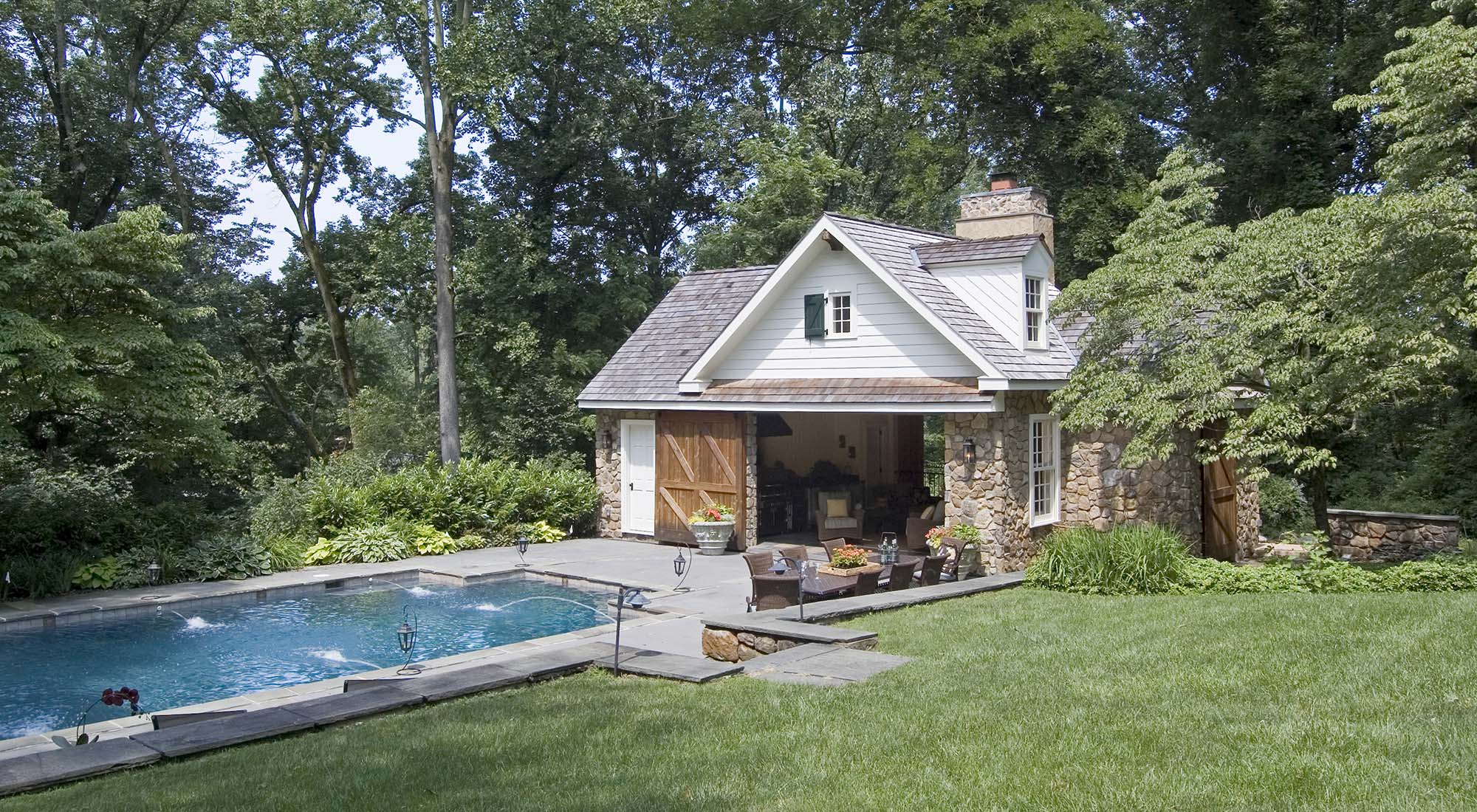 cute country pool house real stone with white siding real wood doors blue stone patio