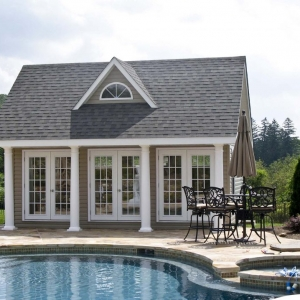 small pool house design with dormer round columns french doors stone pool patio