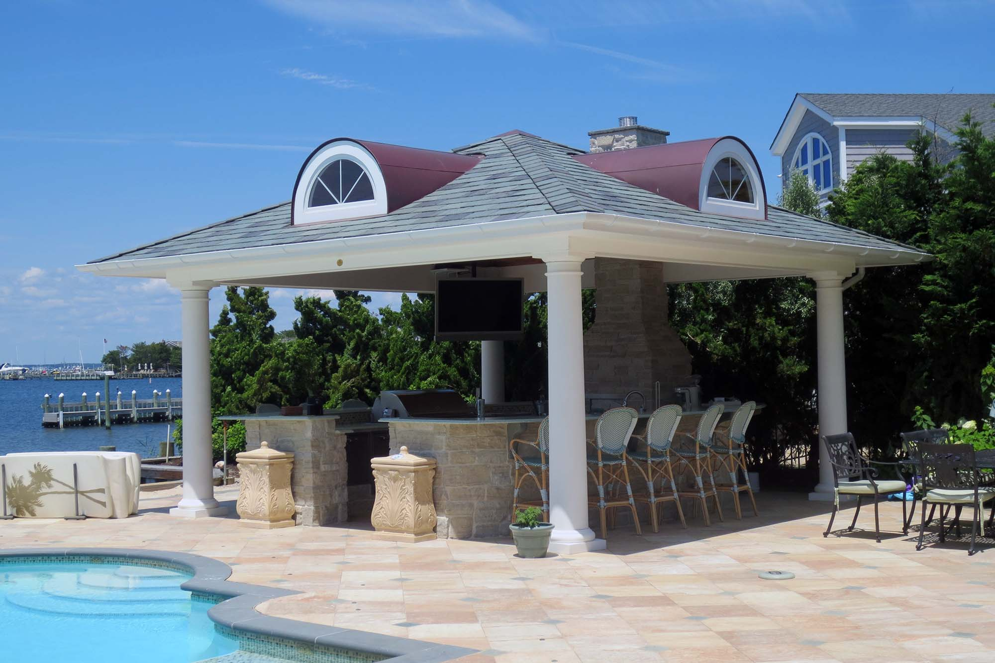 cool pool house 4 round columns outdoor fireplace tv bar grill outdoor kitchen stools tile patio