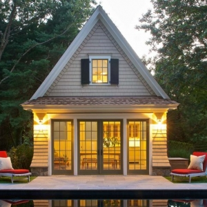 small pool house style cedar shake with steep roof stone patio glass wall