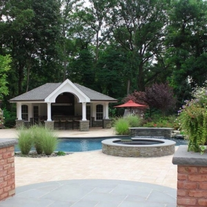 pool house design with huge patio pavers and blue stone brick pillars in ground pool real stone
