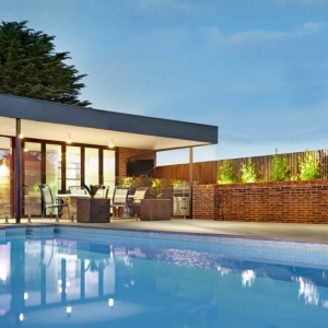 modern flat roof pool house design red brick with wood trim negative edge swimming pool